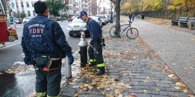 Firemen at hydrant with a wrench shut water with bMHR hotrod bicycle watching image
